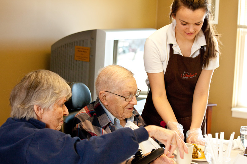 employee serving a meal to residents