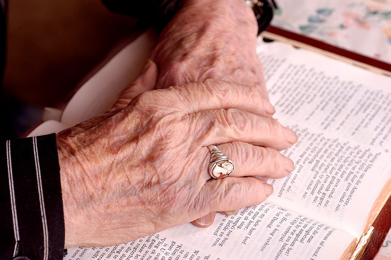 Auburn Manor resident's hands on a Bible